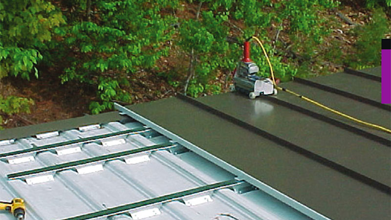 A-new-brown-standing-seam-metal-roof--panel-is-being-installed-over-an-existing--screw-down-metal-panel-using-Notched--Sub-Purlins